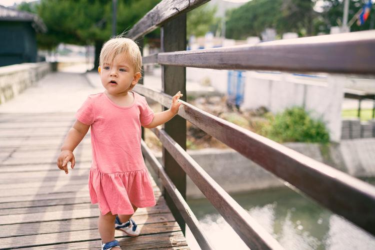 Full length of cute girl standing on railing