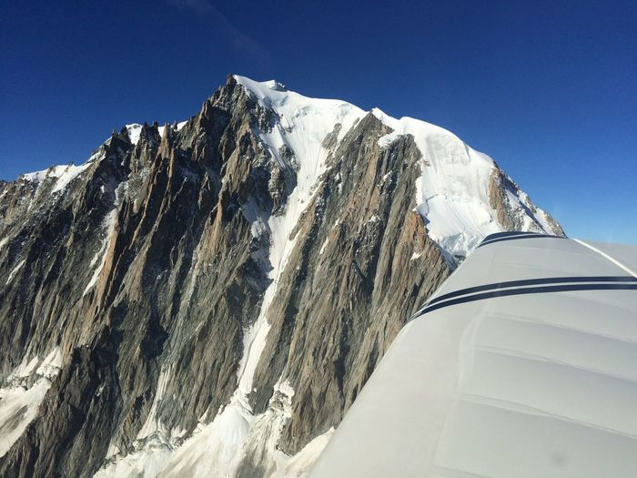 View of snowcapped rocky mountain by airplane wing
