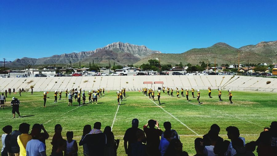 People on field by mountains against clear blue sky