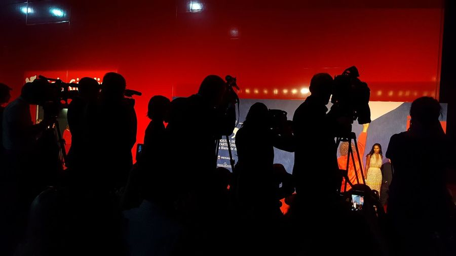Silhouette people with television camera at studio