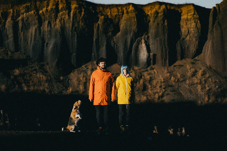 Rear view of a couple and a dog standing on rock