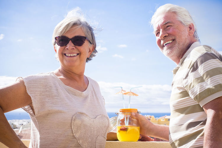 Smiling couple having drink while standing against sky