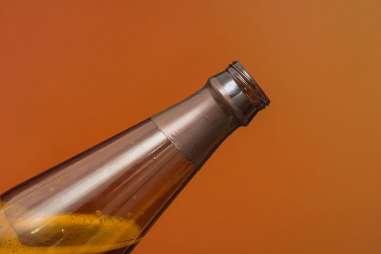 Close-up of wineglass on table against orange background