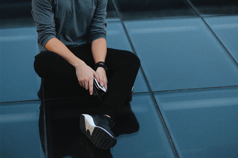 Low section of man holding mobile phone while sitting on floor