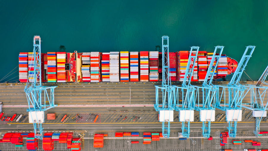 Multi colored chairs at commercial dock against blue sky
