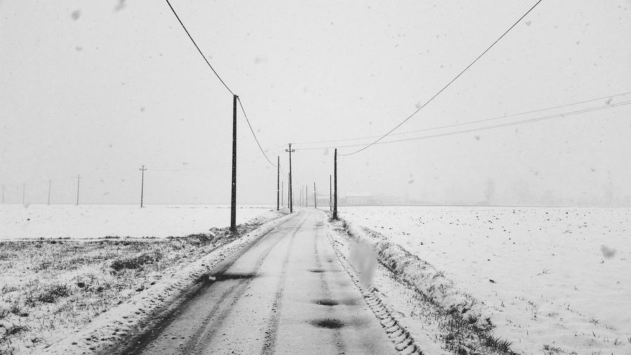 Road amidst snow covered land against sky
