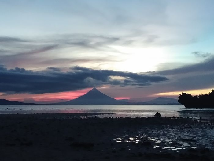 Mayon volvano view during sunset. Water Sea Sunset Beach Power In Nature Nautical Vessel Blue Lightning Sky Horizon Over Water Romantic Sky Geyser Moody Sky Dramatic Landscape Volcanic Landscape Dramatic Sky Seascape Atmospheric Mood Cloudscape