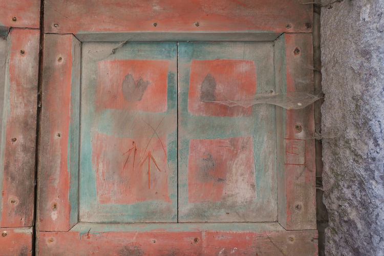 pastel red colored door Architecture Built Structure Closed Day Door Entrance Metal Nail No People Old Outdoors Red Text Wall Wall - Building Feature Weathered Western Script Wood - Material