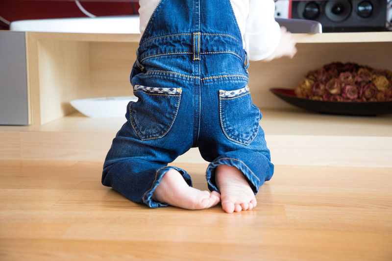 Low Section Of Child Kneeling On Hardwood Floor