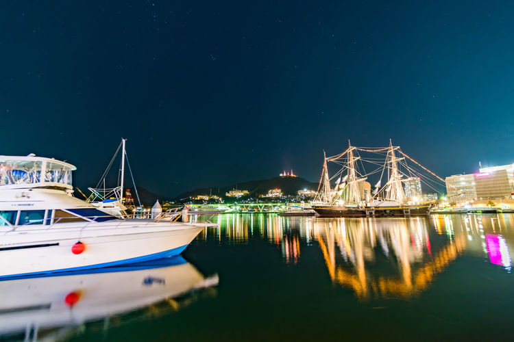 Boats moored on river against sky at night