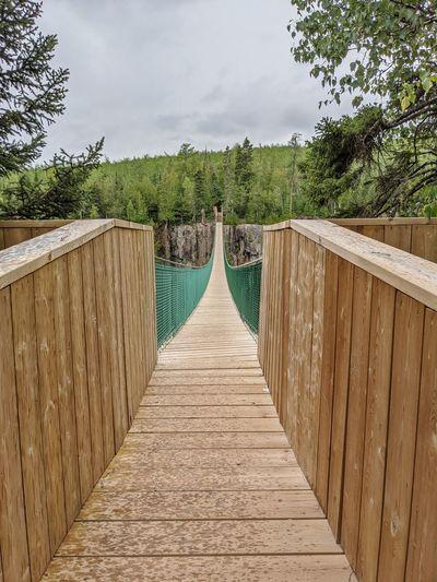 Wooden footbridge leading to water against sky