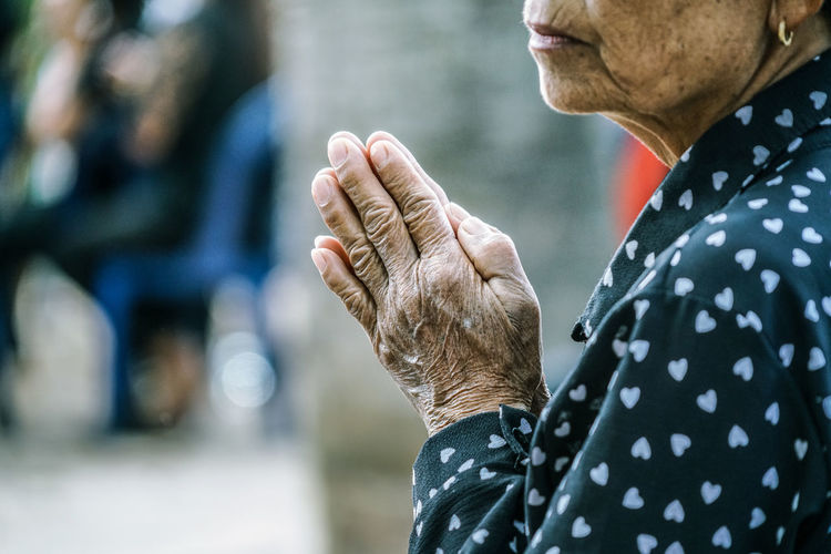 Midsection of senior woman with hands clasped praying at temple
