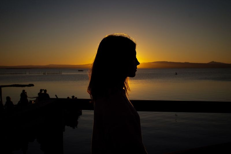 Shape Focus Focus On Foreground Shadow Sunlight Sun Water Girl Sunset Sky Water Silhouette Women Real People Orange Color Leisure Activity Adult Lifestyles Beauty In Nature Nature One Person Sea Scenics - Nature Beach Standing Outdoors Incidental People Autumn Mood