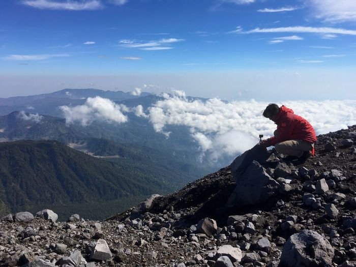 Woman Crouching While Arranging Monopod On Scenic Mountain Range Against Sky