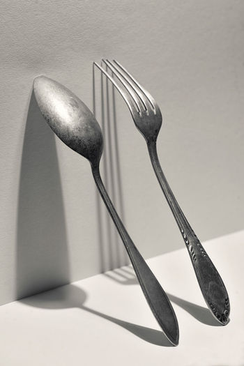 Close-up of fork and spoon on table against wall
