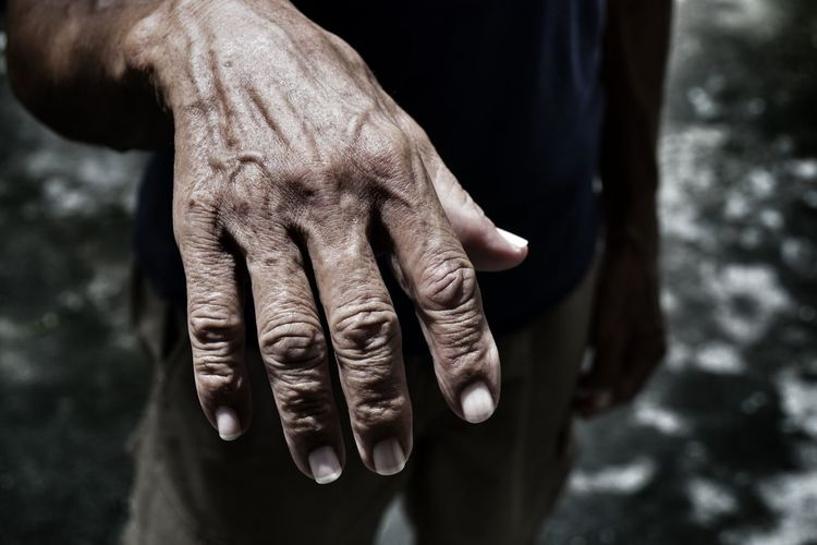 Midsection of man showing wrinkled hand