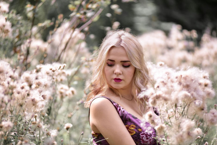 Closed-up of beautiful young woman with blond hair standing amidst flowers
