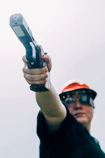Low angle view of woman shooting with pistol against clear sky