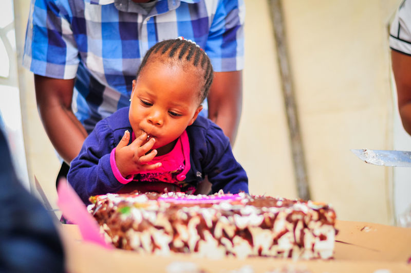 Girl Licking Birthday Cake At Home