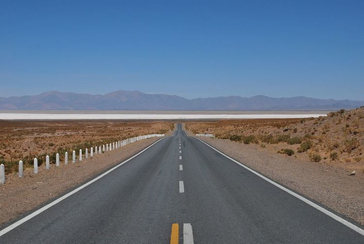 Straight road towards salinas grandes high up in the andes of argentina