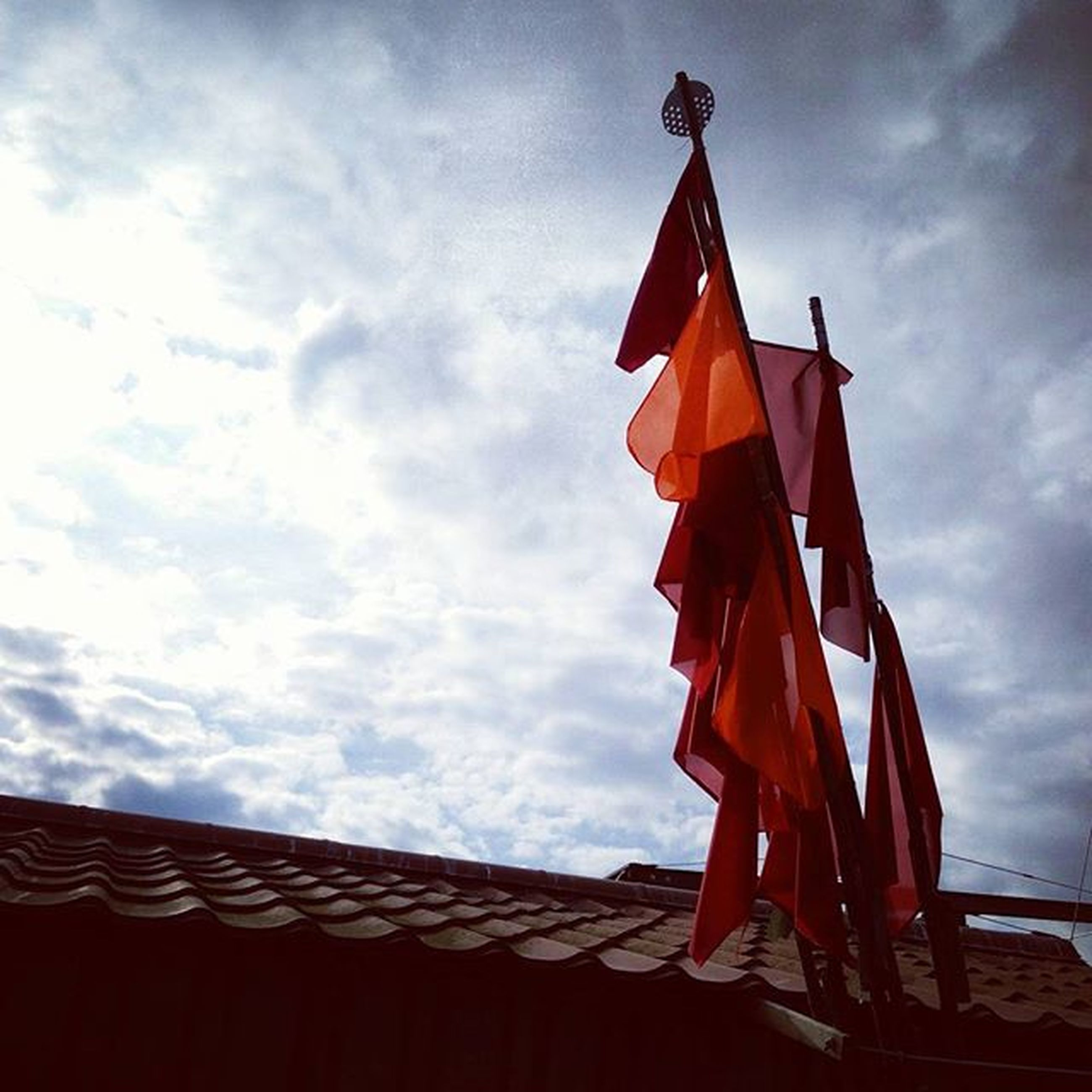 sky, low angle view, cloud - sky, flag, cloud, cloudy, patriotism, red, built structure, identity, national flag, architecture, protection, building exterior, day, outdoors, wind, safety, religion, high section