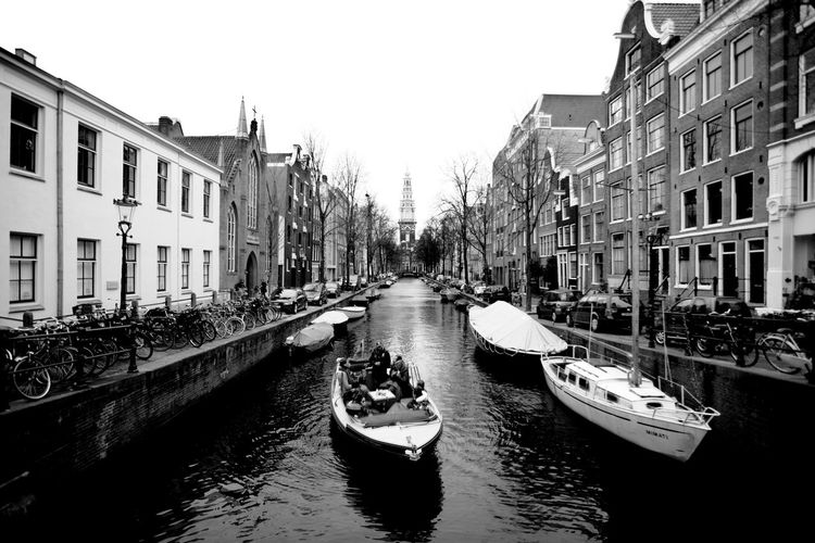 Boats Moored In Canal Along Buildings