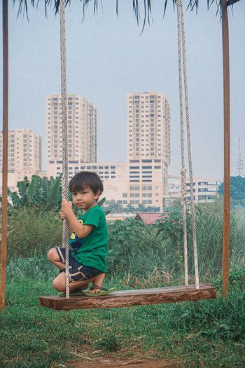 Full length of boy sitting on land against clear sky