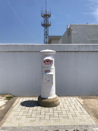 Telephone booth by building against sky
