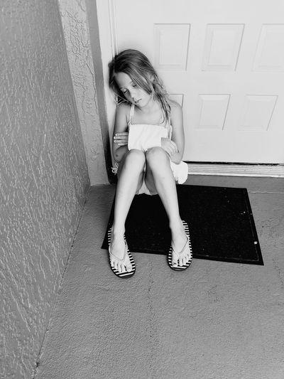 High angle full length of girl sleeping wile sitting on doorway