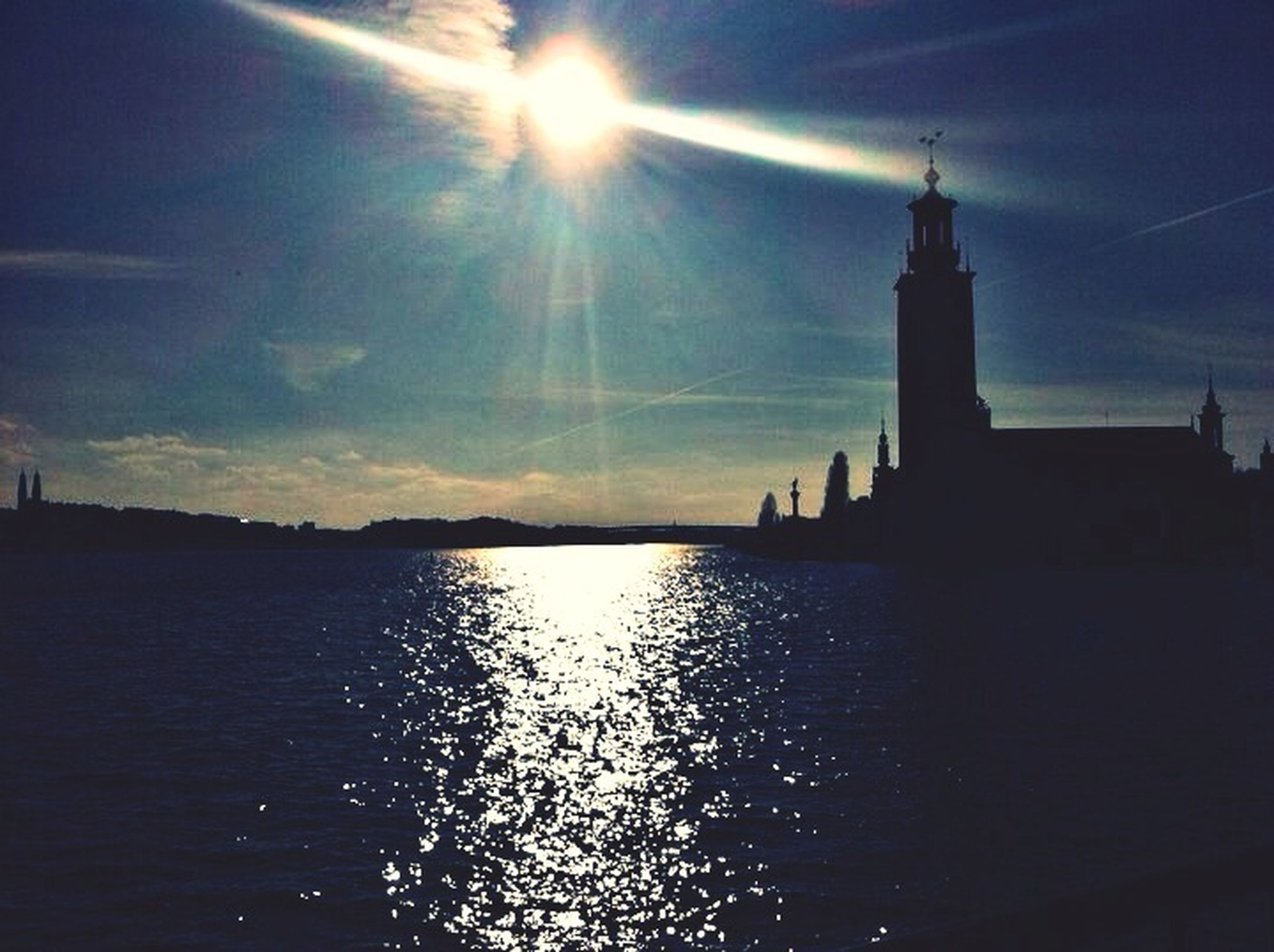 architecture, water, built structure, sky, silhouette, building exterior, waterfront, sun, sunset, reflection, river, sunlight, tower, rippled, sea, lighthouse, cloud - sky, cloud, travel destinations, sunbeam