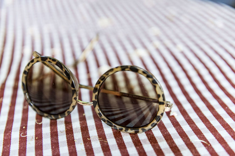 Close-Up Of Sunglass On Tablecloth