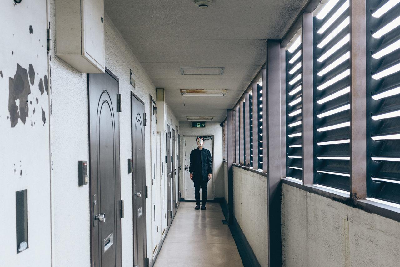 Man wearing animal mask in corridor