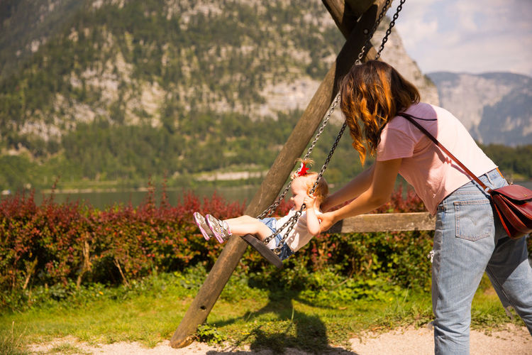 Side view of mother swinging girl in playground