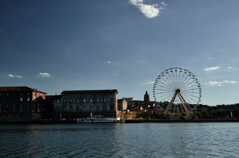Ferris wheel by river and buildings against sky