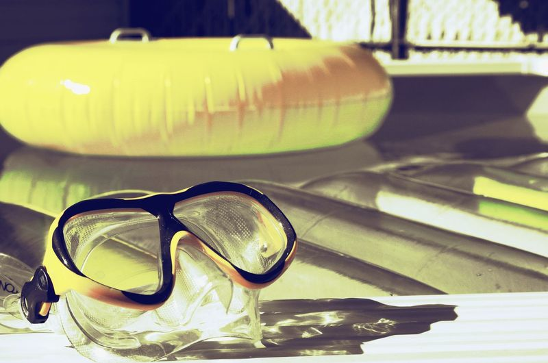 Swimming goggles at poolside during sunset