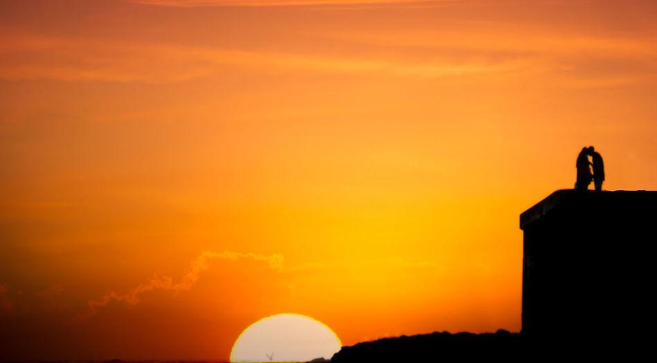 Silhouette of man against orange sky