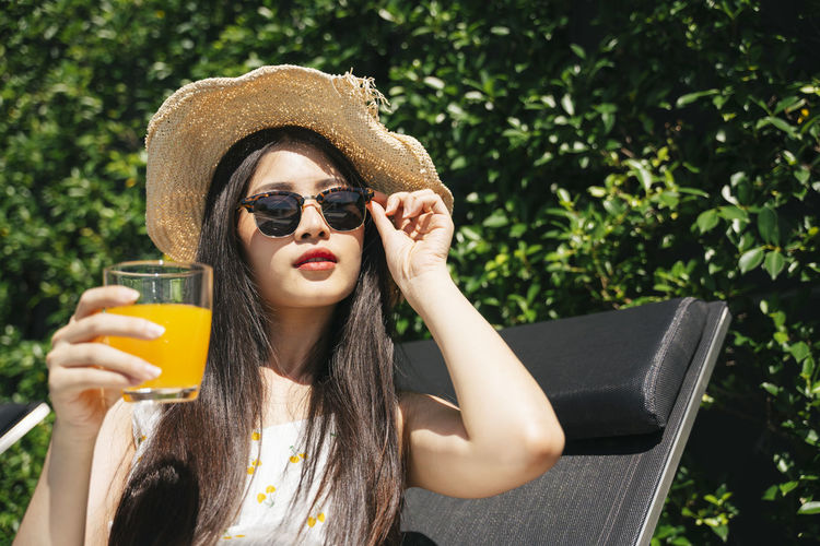 Portrait of young woman holding juice while sitting outdoors