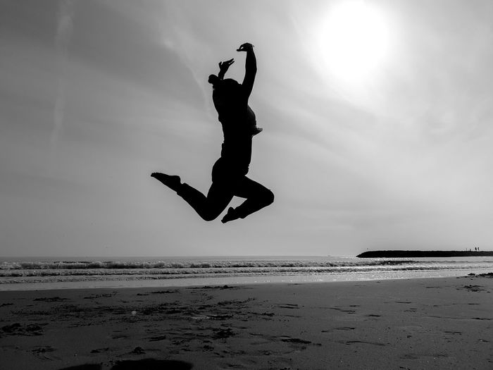 Silhouette man jumping at beach against sky