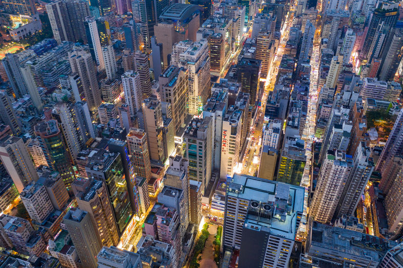 Aerial view of illuminated street amidst buildings in city at night