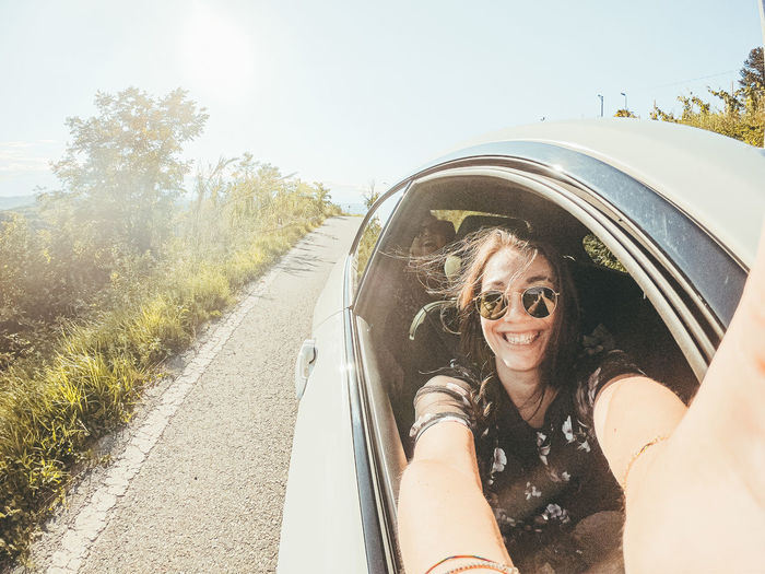 Portrait of smiling woman doing selfie while sitting in car