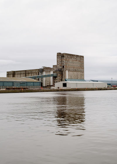 Water Sky Built Structure Architecture Waterfront Building Exterior Transportation Mode Of Transportation Cloud - Sky Reflection No People Day Nautical Vessel Sea Harbour Harbour Side Concrete Storage Compartment Warehouse Warehouse District Brutalism Brutalist Architecture Industry Industrial Depot