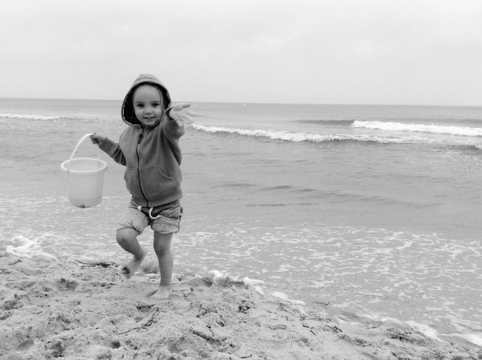 Portrait of girl holding bucket at beach