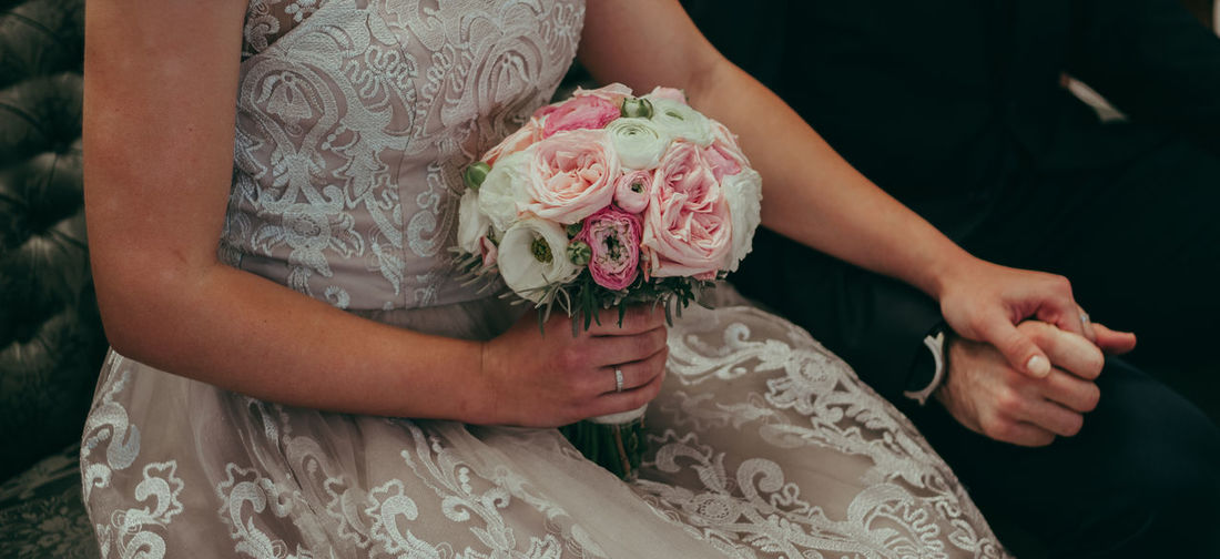 Midsection Of Bride Holding Bouquet And Groom Hand