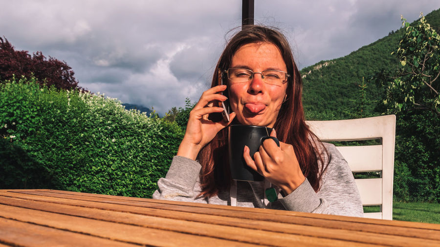 Portrait of woman talking on phone while making face sitting outdoors