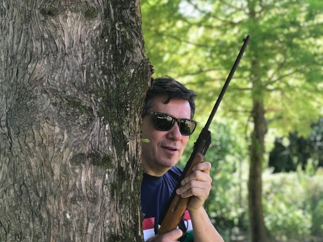 The hunter is waiting for his prey Tree Glasses One Person Plant Leisure Activity Real People Sunglasses Lifestyles Young Men Portrait Holding Tree Trunk Trunk Casual Clothing Fashion Young Adult Land Front View Day Nature
