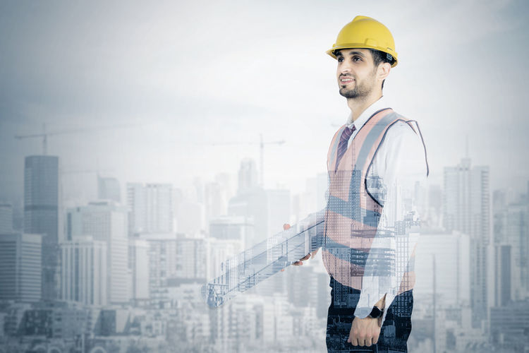 Digital composite image of architect and scaffolding against sky