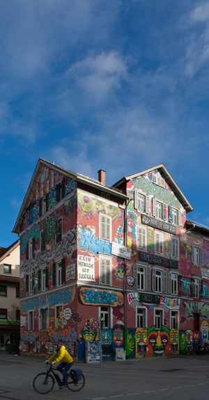 Building Exterior Architecture Built Structure Transportation Mode Of Transportation City Sky One Person Cloud - Sky Land Vehicle Building Street Bicycle Real People Road Men Graffiti Residential District Day Outdoors Riding Mural My Best Photo Streetwise Photography