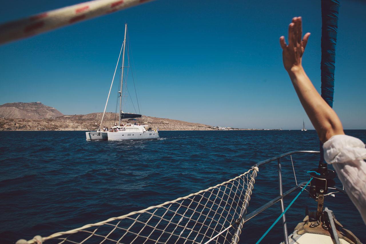 Cropped image of woman waving in aegean sea against sky