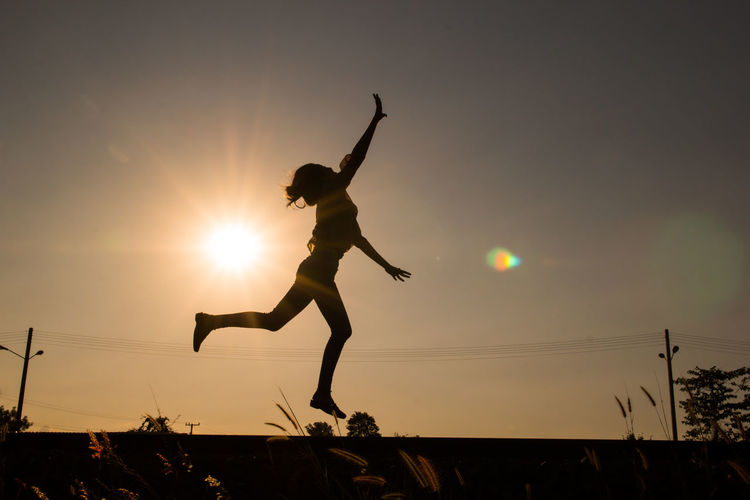 Woman man jumping against sky during sunset
