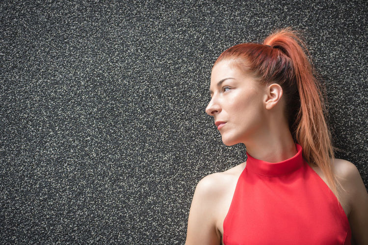 Portrait of woman standing against red wall